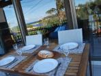 outdoor dining on balcony overlooks ocean and reserve