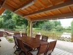 une terrasse couverte avec barbecue  avec vue sur l'étang et la campagne environnante