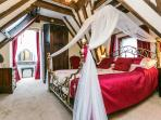 Romantic bedroom with canopied bed. View through to bedroom turret