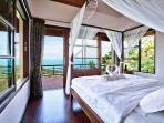 Master bedroom with four poster king sized bed .