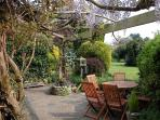 The wisteria clad pergola provides an attractive sitting-out area