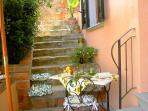 Stone staircase and a private terrace with umbrella table and chairs