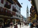 People go shopping in the main street in the city centre. Bloomy buildings surround the bell tower