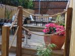 Garden deck for al fresco dining, with 2 large tables, 12 chairs, and BBQ