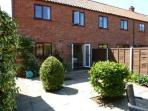 Rear private gardens of Malthouse Court with patio doors leading from lounge/diner