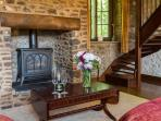 Spacious lounge with beamed ceiling and gas fire in an inglenook