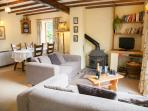 Spacious living room with exposed beams, multi-fuel stove and dining area