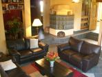 Gigantic guest lounge with traditional wood burning tiled stove, and large screen TV