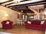 Comfortable living area with exposed stone walls, oak beams, oak flooring, log burner, British TV