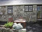 There is a pretty patio at the back of Amy cottage with garden furniture.