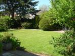 Lawn surrounded with mature trees and shrubs for summer games. Apples a plenty to eat or take home