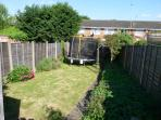 Rear garden which has a patio area plus steps down to a lawn with trampoline