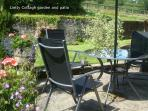 Lletty Cottage private  patio  set in pretty garden with  flowers and lawn- a delightful sun trap.