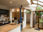 Kitchen and study area beyond, opening up onto enclosed deck area