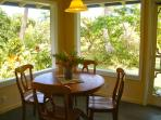 The dining table in the screened lanai, surrounded by tropical foliage