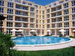Flores Park Apartment Complex. Lounge and bedrooms overlook the  pool. Balcony with table + chairs.