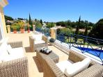 First floor terrace with views accross pool and garden to nearby golf course beyond
