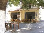 "Traditional ""kafeneion"" (small coffee shop) in the village under the shade of the old plan"