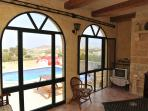 Sitting room looking over pool and pool area and views of the village of Gharb
