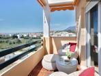 Vista de terraza inferior: zona de salida del dormitorio ppal con sillones de mimbre y vistas al mar
