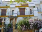 Fachada principal: patio delantero ajardinado, arquitectura mediterránea, terrazas en dormitorios