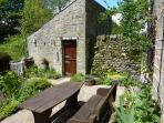 Pretty cottage garden with seating for 4 people. Outbuilding housing the utility room.