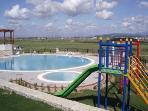 Pools and children's play area with mountain views