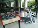 A disposition table de ping-pong, baby-foot, tapis de marche et vélo elliptique