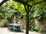 Walled courtyard with leafy wisteria covered pergola - a very private retreat