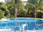 Pool area with large main pool and smaller children's pool surrounded by lush well kept gardens