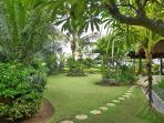 Bali Sea Villas - North Bali. View of tropical gardens toward the villa terrace, pool and beach.