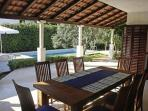A1 - Covered terrace with large teak table and a view of the pool - A1 apartment