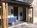 The sunny dining porch with bio fold doors opening onto a patio and garden