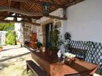 Al lado de la barbacua hay un patio cobierto, con una mesa de madera.