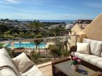 Relax on the beautiful terrace with views over the pool and golf course down to the sea