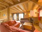 The living room is spacious and comfortable with a log fireplace and a balcony