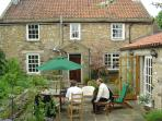 The Courtyard Garden - shows outside furniture, patio doors to sun room & front door/porch.