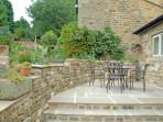 Walled patio area with outdoor furniture
