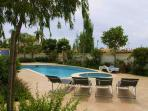 View of pool area with provided sun loungers