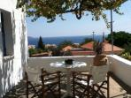Enjoy the view of the sea from the large veranda with grape vines
