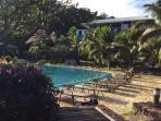 Les chaises longues autour de la piscine, face à l'océan
