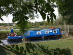 A narrow boat passing your cottage at Robertstown Holiday Village