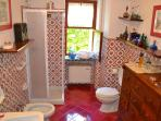 Orange bathroom, with shower. Towels, linens, bathrobes.