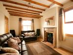 Characterful beamed sitting room with log burner