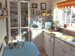 Kitchen with electric oven, fridge, microwave, toaster, kettle and radio. Well stocked