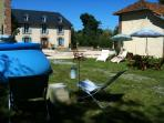 Large adult splash pool with bar-b-que gazebo and lounge areas within garden spaces.