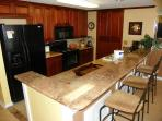 The kitchen has granite counter tops, breakfast bar and is open to the dining and living areas.