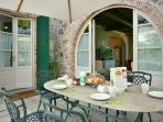 Outdoor stone breakfast table with large parasol, just by the kitchen & near garden playground area.