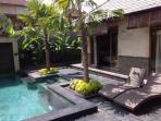 Volcanic stone deck bordering house & pool.