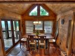 Dining area that opens up to the screened in porch and picnic table